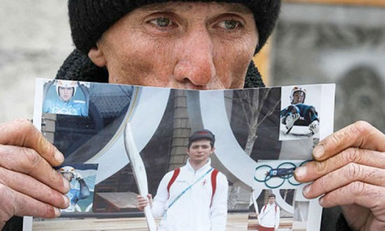 Nodar Kumaritišvili's father, David holds up a picture of his son